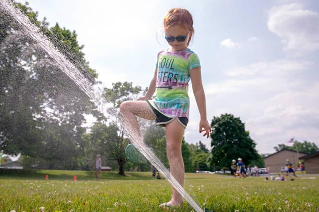 <p>Kindergartner Emma Thomas rinses off her feet.  </p>