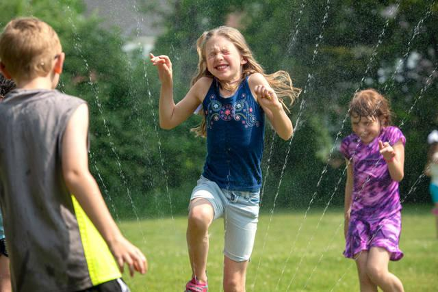 <p>Second-grader Tatiana Casey-Holowka runs trough the sprinkler.  </p>