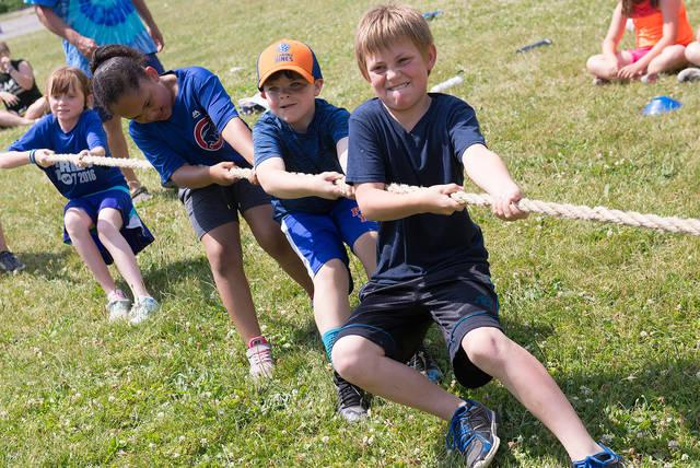 <p>Fifth-grader Kaleb Bryan of St. Michael School in Penn Yan works with teammates in a tug-of-war contest during the school's annual Field Days June 18. (Courier photo by John Haeger) </p>