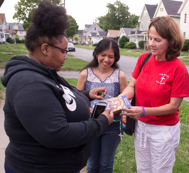"<p>Members of a ""Missionaries of Peace"" team from Rochester's Holy Apostles Church hand out a rosary to a Rochester resident Aug. 2.  </p>"