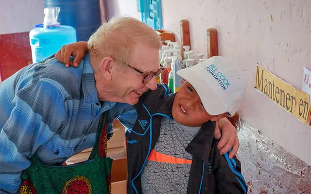 <p>Bill Cook gives a hug to Jose, a child with Down syndrome, during a May visit to Huanaco, Peru. Through his nonprofit foundation, Cook works to provide educational opportunities for some of the world's poorest children. (Photo courtesy Bill Cook) </p>
