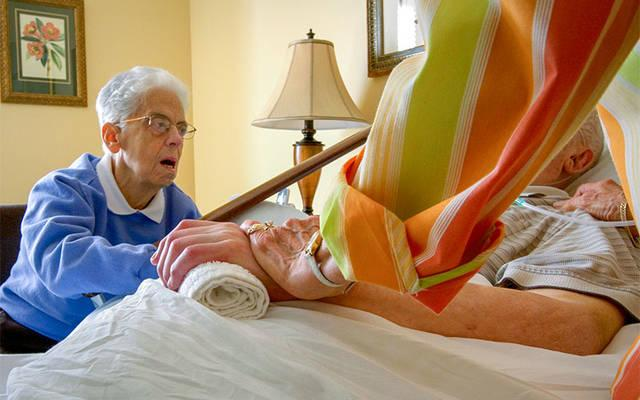 <p>In this Sept. 7, 2012, file photo, family members watch over Leo King at his bedside at the Center for Compassionate Care in Pittsburgh. King, an 84-year-old urologist and veteran of World War II, died the following day with family at his side. Pictured is his sister Patricia King, left, and his wife, Jacqualin, right. (CNS photo/Nancy Phelan Wiechec) </p>