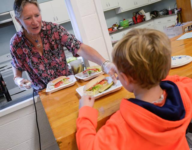 <p>Mary Margaret Loman serves a sub sandwich to a student at St. Francis-St. Stephen School in Geneva Sept. 20. (Courier photo by John Haeger)  </p>