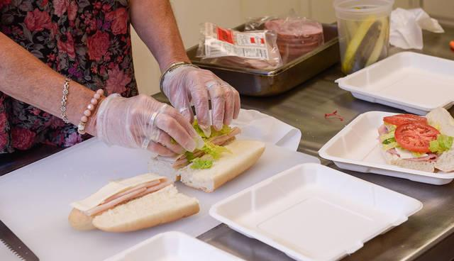 <p>Mary Margaret Loman makes sub sandwiches for students at St. Francis-St. Stephen School in Geneva Sept. 20. (Courier photo by John Haeger)  </p>