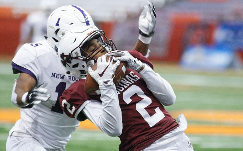 Aquinas's Kobe McNair (2) makes the catch as New Rochelle (19) Shemar Morgan reaches to make the tackle in the NYSPHSAA Class AA Championship in Syracuse Nov. 24. Aquinas Institute won the title 21-14. (Courier photo by John Haeger)