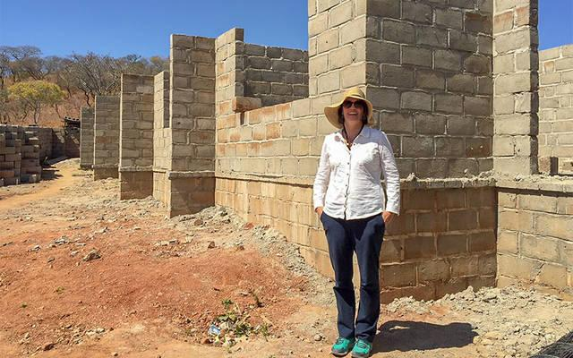 <p>Melissa Bryant poses in front of a future community library in Zambia in 2016. (Photo courtesy of Melissa Bryant)  </p>