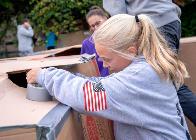 <p>Eleven-year-old Sierra Ford of St. Catherine of Siena assembles her cardboard shelter. (Courier photo by Jeff Witherow)  </p>