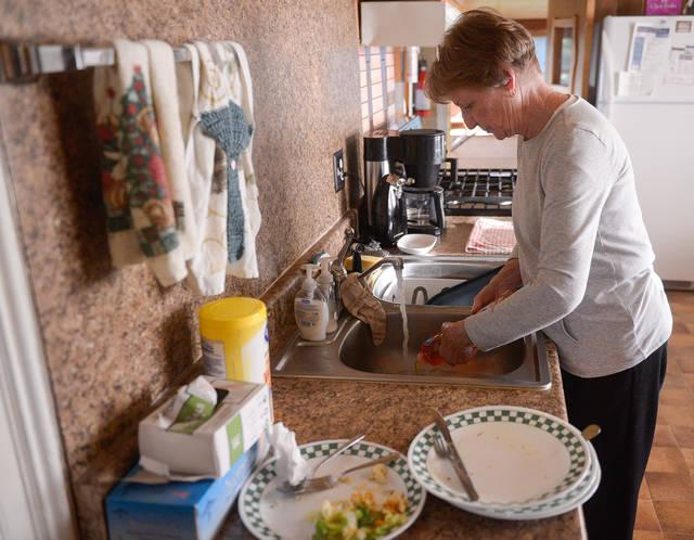 <p>Jane Kelly, a parishioner of St. Patrick Church in Victor, prepares to wash dishes after serving dinner at the Canandaigua Veterans Club Oct. 9. (Courier photo by John Haeger) </p>