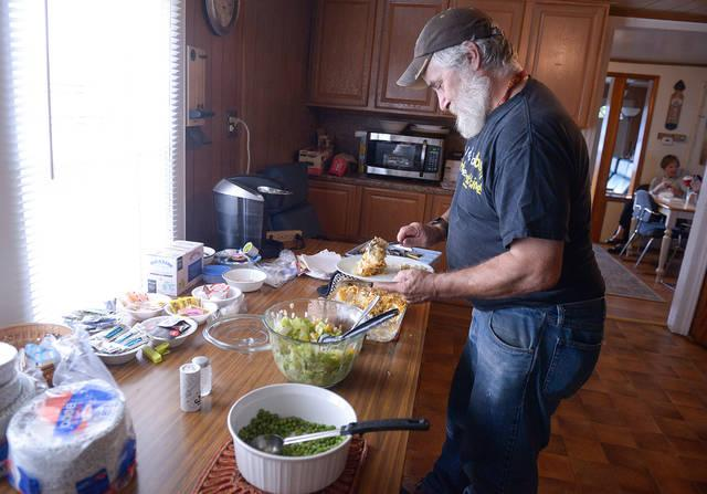 <p>Veteran Tom Bellwood fills his plate during an Oct. 9 dinner at Canandaigua Veterans Club. (Courier photo by John Haeger)  </p>