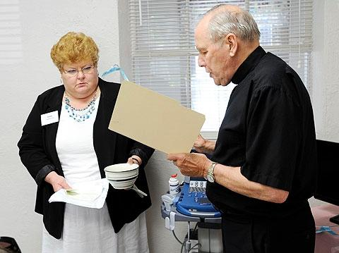 Bishop Matthew H. Clark blesses an ultrasound machine during a June 20 dedication ceremony at His Branches Health Services in Rochester.Looking on is Jann Armantrout, diocesan life-issues coordinator.