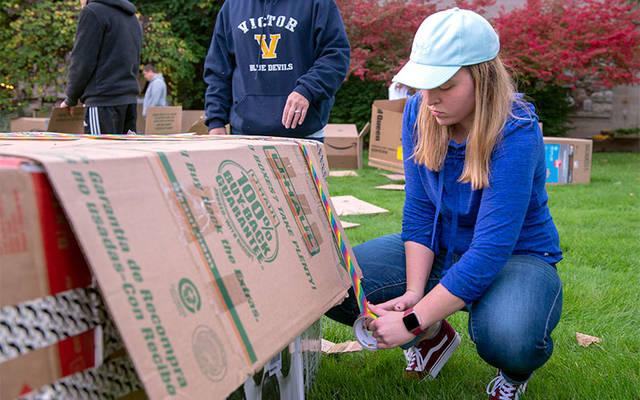 <p>Kristen Leschhorn, youth and young-adult minister at St. Patrick Church in Victor, tapes together her cardboard shelter Oct. 13 at St. Catherine of Siena Church in Mendon. (Courier photo by Jeff Witherow)  </p>