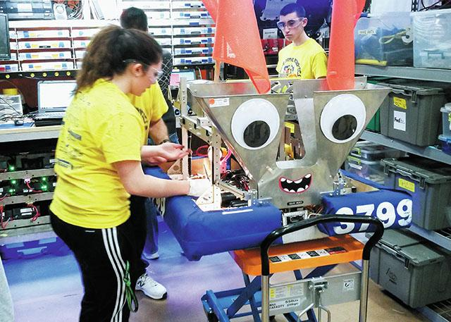Team members of Elmira Notre Dame High School's robotics team make adjustments on their robot March 17 during the Finger Lakes Regional FIRST event at the Rochester Institute of Technology.