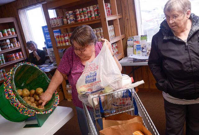 <p> Volunteer Carol Boughton (left) helps Marge Bellinger fill her cart with food Nov. 26 at Tioga County Rural Ministry's food pantry.  (Courier photo by John Haeger) </p>