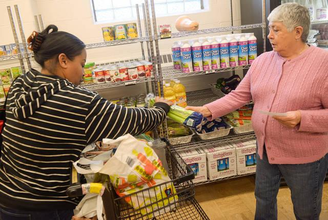 <p>Perdomo Carmen (right) helps Tammy Liddell as she receives food at the Sister Regis Food Cupboard Nov. 19 in Rochester. (Courier photo by John Haeger)  </p>
