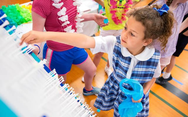 <p>Eight-year-old Adriana Robinson plays Plinko during the June 8 Mission Day at St. Louis School in Pittsford. </p>