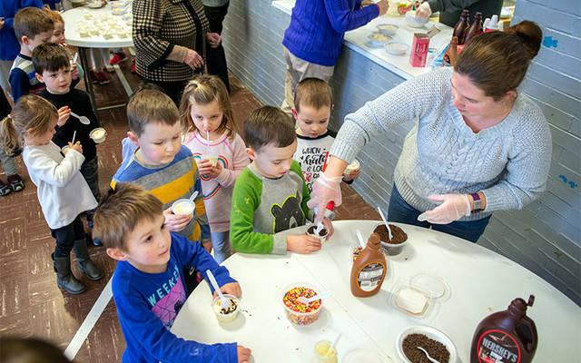 <p>Parent volunteer Jennifer King tops sundaes during a Catholic Schools Week ice cream party at All Saints Academy in Corning Jan. 29.  </p>