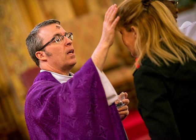 "Father William ""Mickey"" McGrath distributes ashes during an Ash Wednesday Mass at Rochester's St. Michael Church March 1. Several parishes are using the themes of the V National Encuentro as a jumping-off point for reflections during Lenten gatherings this year."