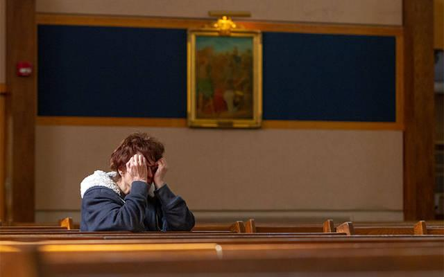 <p>A parishioner of Our Mother of Sorrows in Greece kneels in prayer during the 2014 Day of Penance and Mercy.  </p>