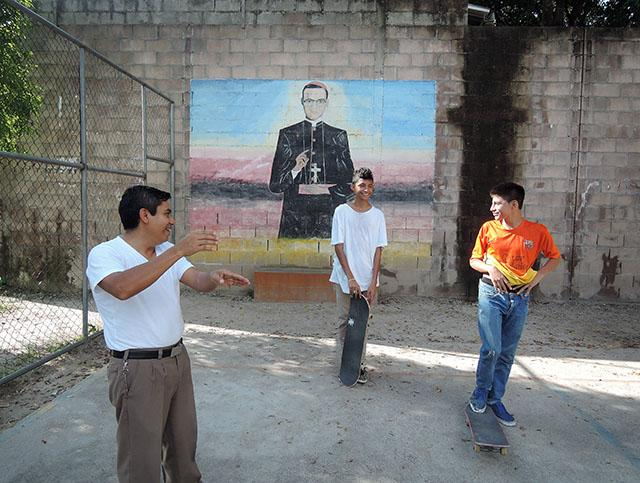 Father Salomon Perez speaks with two young skateboarders in a recreational facility he had built next to the St. Joseph of Flores Parish in Tonacatepeque, El Salvador. Parishioners suffered from gang-related crime committed until Father Perez negotiated a truce. El Salvador has had many children leave due to violence and attempts at forcibly recruiting them into gangs.