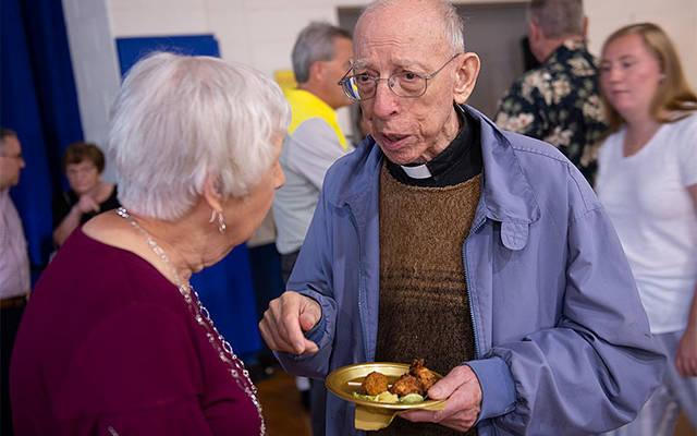 <p>Basilian Father Joseph Trovato talks with Peggy MacAdami during a June 29 gathering at Christ the King Church in Irondequoit. The event honored the conclusion of the Congregation of St. Basil's long service in Irondequoit. (Courier photo by John Haeger) </p>