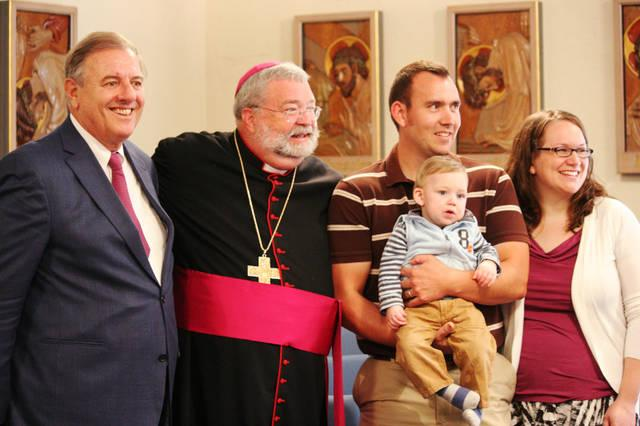 <p>In this photo from September of 2011, James Fulton Engstrom is held by his parents, Travis and Bonnie Engstrom, at the Spalding Pastoral Center in Peoria, Ill., as a tribunal began to investigate the boy&rsquo;s miraculous healing through the intercession of Archbishop Fulton J. Sheen. With them are Andrea Ambrosi, postulator of Archbishop Sheen&rsquo;s sainthood cause, and Peoria Bishop Daniel R. Jenky. (CNS photo by Jennifer Willems)  </p>