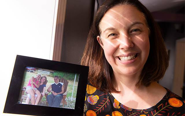 <p>Renae Carapella-Johnson holds a June 2005 photo of herself, her sister Holley and her brother Raymond. Raymond&rsquo;s suicide in October 2005 inspired Carapella-Johnson to become a counselor, and she now operates Ray of Light Counseling and Consulting in Savona. (Courier photo by John Haeger)   </p>
