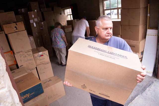 <p>Bob Peterson carries a box of donated items to be packed into a truck at St. Patrick Church in Seneca Falls Aug. 24. The items will be distributed to the needy in Nicaragua. (Courier photo by John Haeger)  </p>