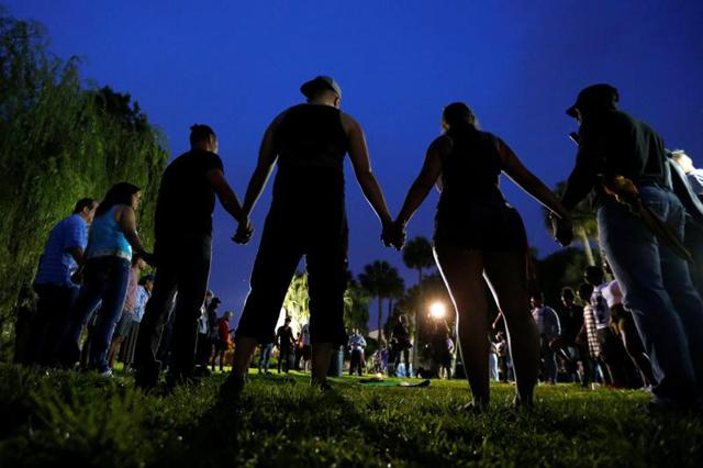 People hold hands in a circle during a June 12 vigil in an Orlando, Fla., park following a mass shooting at the Pulse gay nightclub in that city earlier that morning.