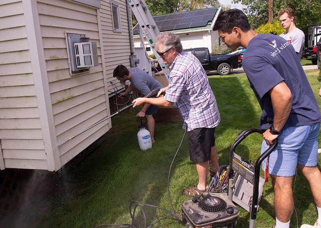 <p>Cornell University men&rsquo;s hockey coach Mike Schafer shows forward Noah Bauld how to use a power washer Sept. 22 during a service project to help senior citizens with outdoor chores. The project took place in conjunction with All Saints Church, Lansing; St. Anthony, Groton; and Holy Cross, Freeville/Dryden. (Courier photo by John Haeger)  </p>