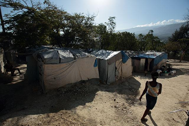 A woman walks past makeshift tents in late November in Port-au-Prince, Haiti.  Nearly five years after one of the most devastating earthquakes ever to rock the Western Hemisphere, more than 85,000 people still live in dozens of tent camps across Haiti's expansive earthquake zone.