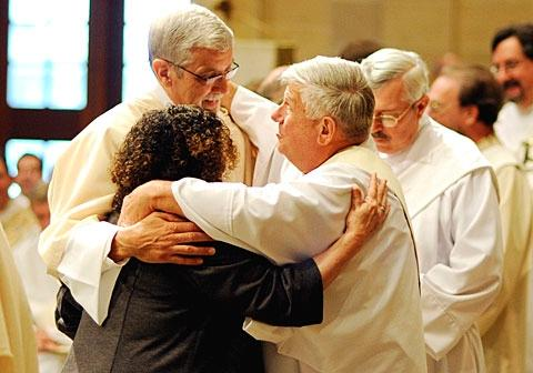 Newly ordained Deacon John Hoffman (left) is congratulated by Deacon Larry Feasel during the June 4 deacon ordination Mass at Rochester's Sacred Heart Cathedral.