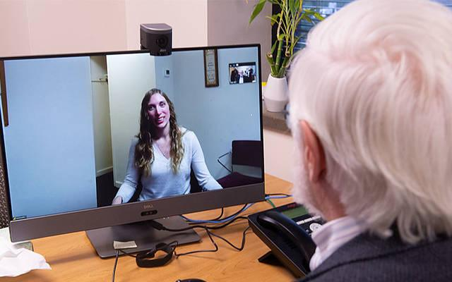 <p>Dr. Robert Young and Jessica Pruitt demonstrate Catholic Family Center&rsquo;s new telehealth capabilities, which allow a staff psychiatrist to visit with a client in one of the agency&rsquo;s three intensive residential drug-treatment centers. (Courier photo by John Haeger)  </p>