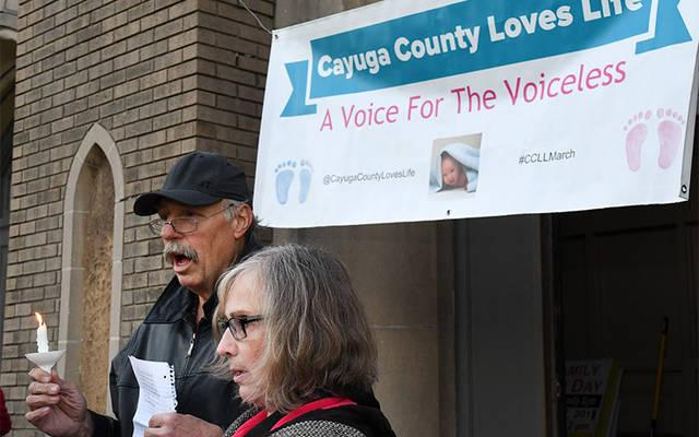 <p>Jon and Karen Quinn speak in front of Holy Family School in Auburn Oct. 18 during a candlelight vigil sponsored by Cayuga County Loves Life. (Photo by Glenn Gaston)  </p>