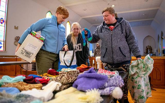 <p>Laurie Baverstock (from left) of Holy Family Catholic Community hands out giving-tree gifts to Bonnie Brooker and Sonya Davis at St. Joseph Church in Wayland Dec. 14. (Courier photo by Jeff Witherow)  </p>