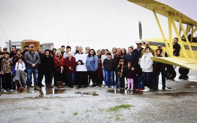 <p>Parishioners of St. Anne Church in Cow Island, La., stand next to the crop duster that had 100 gallons of holy water on it to bless the nearby farms and town. (CNS photo via social media/Diocese of Lafayette)  </p>