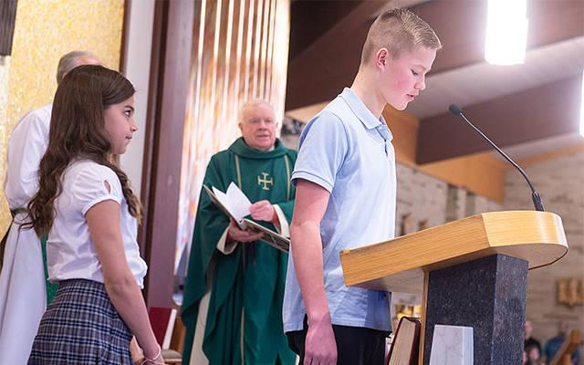 <p>Gavin Earl, a student at St. Joseph School in Penfield, leads the prayers of the faithful as classmate Capriana Carbone looks on during a Catholic Schools Week Mass Jan. 26 at St. Joseph Church. As part of the school&rsquo;s focus on social and emotional learning, students are encouraged to take on liturgical roles during school Masses. (Courier photo by John Haeger)  </p>