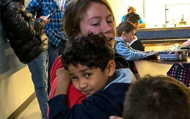 <p>St. Katharine Drexel parishioner Grace Boesel hugs a kindergartner in December during the parish youth group&rsquo;s annual visit to School No. 52 in Rochester. (Photo courtesy of St. Katharine Drexel Parish)  </p>