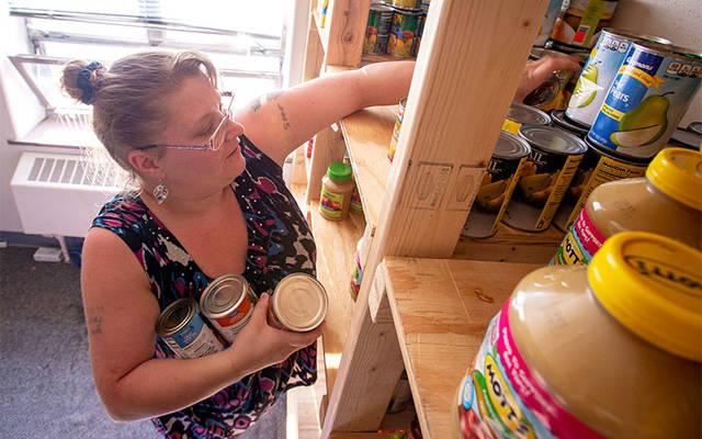 <p>Brenda Hartmetz pulls items from the shelves Aug. 10, 2016, at Joseph&rsquo;s Place, a food pantry operated by Rochester&rsquo;s Cathedral Community. (File photo)  </p>