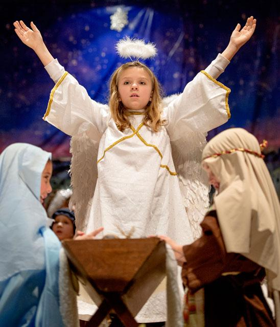 "The Nativity angel, played by second-grader Sarah Glazier, visits Mary and Joseph at the end of ""The Living Creche,"" a Christmas production presented by students at St. Rita School in Webster, Dec. 11, 2014."