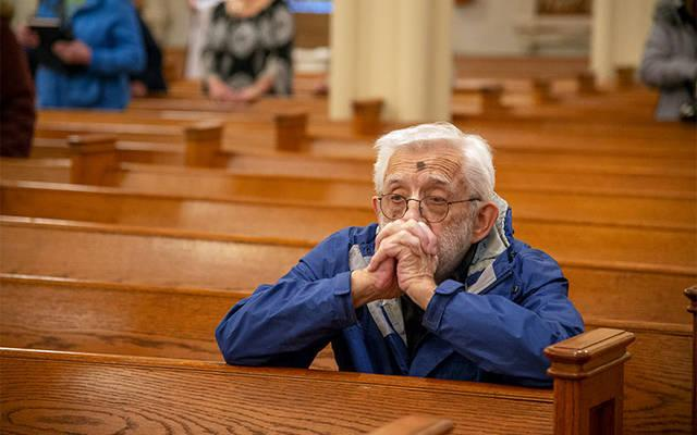<p>Bob Westfall kneels in prayer after receiving ashes during an Ash Wednesday liturgy at St. Agnes Church in Avon Feb. 26. (Courier photo by Jeff Witherow)  </p>