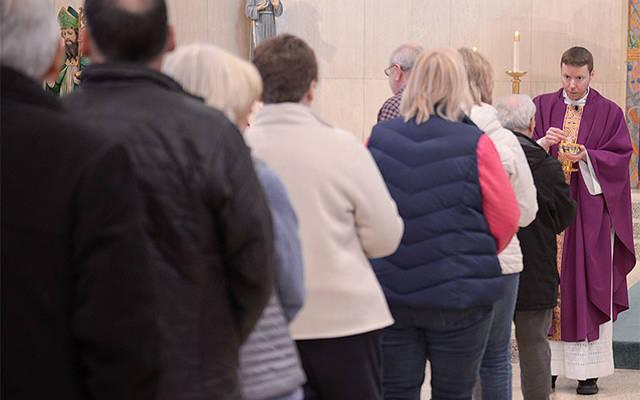 <p>Father Justin Miller distributes Communion during the 10 a.m. Mass at St. Hyacinth Church in Auburn March 14. (Courier photo by John Haeger)  </p>