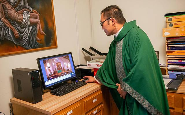 <p>Father Edison Tayag begins the YouTube livestreaming of an Oct. 21, 2017, Mass at St. Patrick Church in Victor. (File photo)  </p>