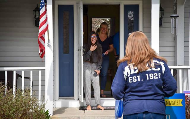 <p>Lisa Costello, counseling coordinator at Our Lady of Mercy School for Young Women, surprises senior Keelan Crowley with a Class of 2020 sign at her home May 1. (Photo courtesy of David Carro)   </p>