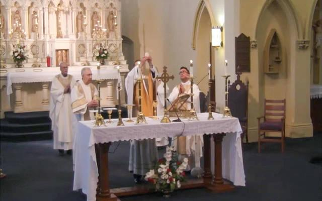 <p>Father Joseph Martuscello elevates the Eucharist during his first Mass of Thanksgiving June 14. (Courier screen capture via YouTube)   </p>