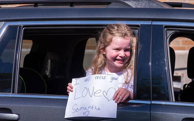 <p>Samantha Miller, a second-grader at St. Joseph School in Auburn, holds a sign out of her car window during a June 17 goodbye parade at the school. (Courier photo by Jeff Witherow)  </p>