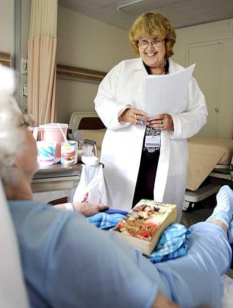 Cheryl Dobson, an assistant in the clinical nutrition office at Hornell's St. James Mercy Hospital, lost 110 pounds after undergoing gastric bypass surgery. Above, Dobson gives dietary advice to a patient June 14.
