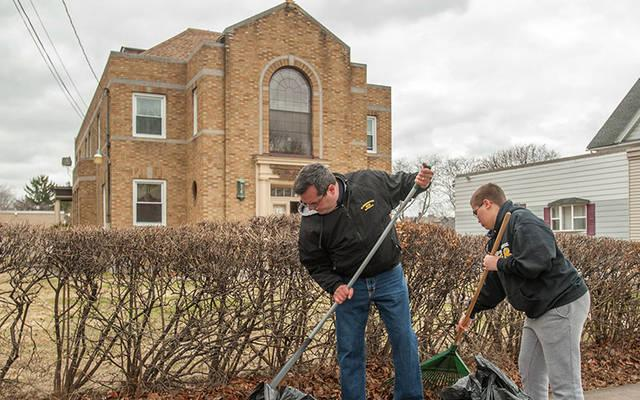 <p> Tom Race and his son Matthew Race, parishioners of Mother of Sorrows in Greece, rake leaves in front of Bethany House April 11, 2015.