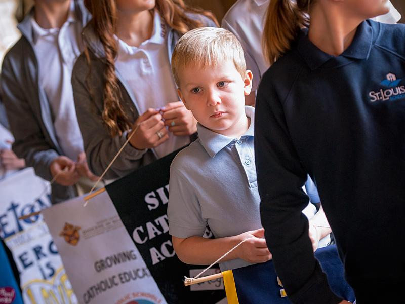Second-grade student Matthew O'Neill waits to process into Rochester's Sacred Heart Cathedral carrying the banner for Canandaigua's St. Mary School before the Catholic Schools Week Mass Feb. 1.