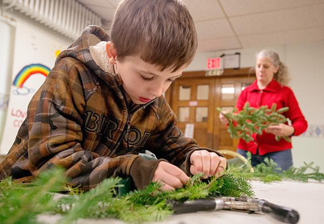 Connor Carter, 7, makes an Advent wreath Nov. 24 with his mother, Brenda Carter, at Phelps' St. Peter Parish.