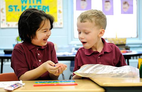 First-graders Angel Molina (left) and Trevor Spears arrange fractions tiles Jan. 22 at Irondequoit'sSt. Kateri School. Catholic schools are adapting to new state and national education standards.